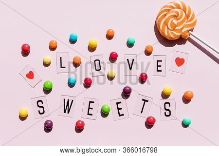 Assortment Of Sweet Candies On Pink Background.colorful Candies And Text Love Sweets.flat Lay Compos
