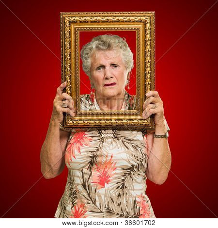 Portrait Of Depressed Senior Woman Holding Picture Frame Isolated Over Red Background poster