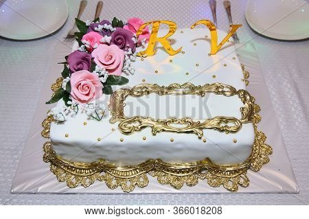 A Place To Write On The Cake. The Letters R And V In Yellow. Pink Flowers On Top Of The Cake. White