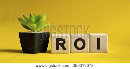 Roi - Business Financial Concept On A Yellow Background. Wooden Cubes And Flower In A Pot.