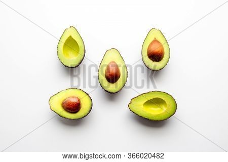 Avocado On A White Background. Cut Avocado With A Stone. Vegetarian Food. Ingredient For Proper Nutr