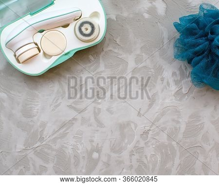 Top View Beauty Tools For Cleansing Or Peeling Face And Body On Concrete Background. Electro Sponge