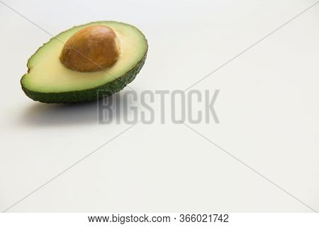 Single Avocado Half With Core. Closeup, Copy Space. Isolated Object On White Background. Fresh Food