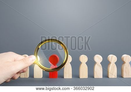 Men With A Magnifying Glass Studies A Red Person In A People Row. Identification, Examination And Is