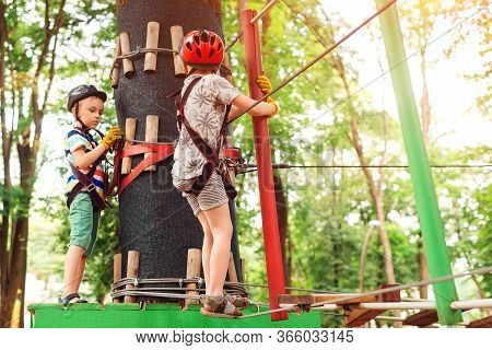 Young Brothers Climbing In High Rope Course In Adventure Park. Children In Forest Adventure Park.