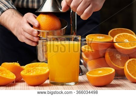 Squeezing an orange with a manual press, close view, making a glass of fresh. Fresh oranges on a wooden table, whole, squeezed and sliced.