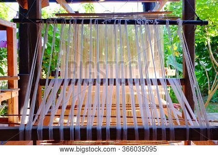 Ancient Weaving Loom With Cotton Fiber Being Made Into Traditional Thai Clothing.
