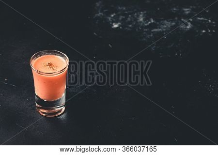 Andalusian Gazpacho In Shot Glass With Black Background With Copy-space.