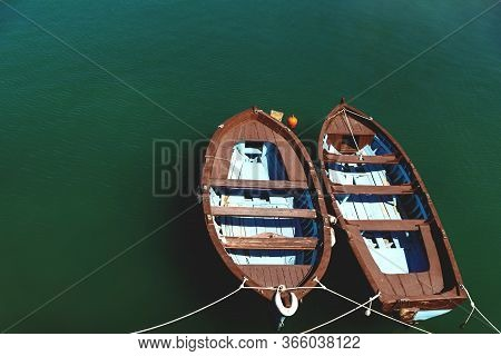 Two Small Brown Blue Wooden Boats On Calm Green Ocean Water, Crete, Greece