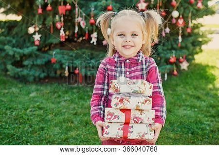 Family Christmas In July. Portrait Of Girl Near Christmas Tree With Gifts. Baby Decorating Pine. Win