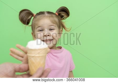 Little Girl 4 Years Old In A Pink T-shirt On A Green Background With Enthusiasm Reaches Out To Ice C