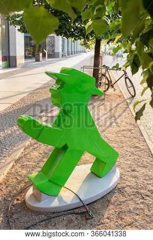 Berlin, Germany - May 18, 2019: Statue of an ampelmann figure with Berlin tv tower at background at sunrise in Berlin, Germany