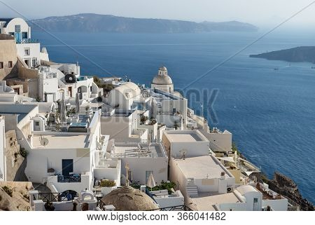 Typical Greek Village With Church Tower At A Sunny Day Lying Far Over The Blue Ocean, Fira, Santorin