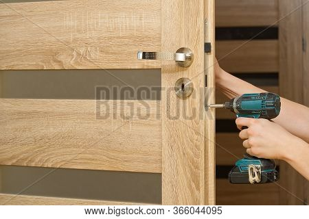 Handyman Repair The Door Lock In The Room. Man Repairing The Door Handle Furniture. Carpenter At Loc
