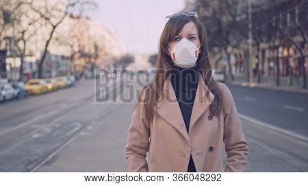 Covid-19 coronavirus protection - Woman in protective face mask in an empty european city.