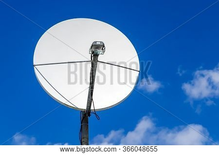 Satellite Dish Against Blue Sky With A Clouds