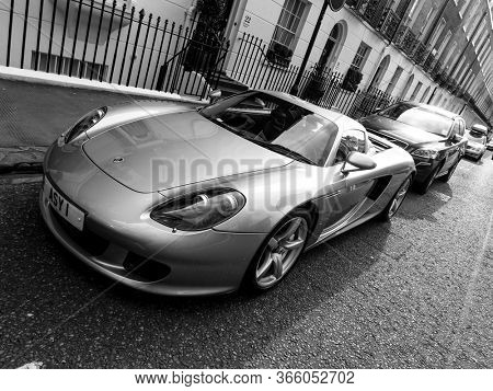 LONDON, UK - CIRCA MARCH 2013: A Porsche Carrera GT parked in the street. The Carrera GT is a mid-engined sportscar produced between 2004 and 2007. Black and white photography.