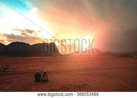 A Couple In Love Is Sitting On The Clean Hot Sand In The Desert At Sunset.admiring How The Sun In Th