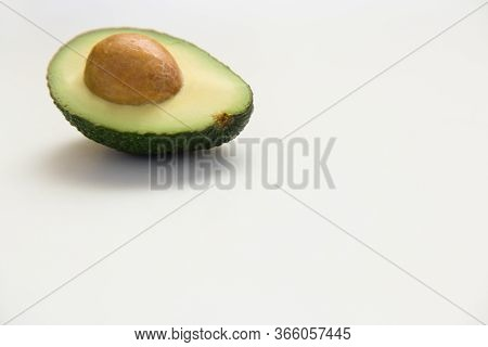 Single Cut Half Of Avocado Fruit With Core. Closeup, Copy Space. Isolated Object On White Background