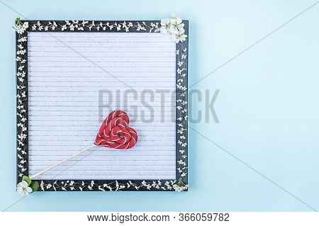 Candy On A Stick In The Shape Of A Heart On A Writing Board, Which Is Decorated With White Small Flo