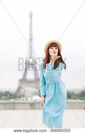 Paris Eiffel Tower. Pretty Caucasian Woman In Hat And Blue Dress, Smiling Happy And Making Air Kiss