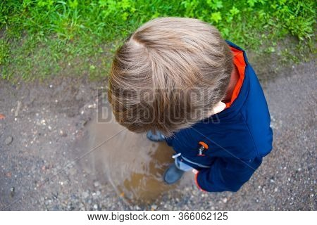 A Boy Stands In A Muddy Puddle. The Child Is Happy In A Wet Puddle. A Happy Childhood Outside.