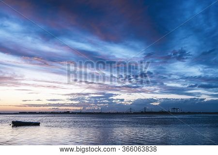 Silhouette Of A Traditional Fisherman Wooden Boat At Dusk On The Calm Water Of The Bay Os Cadiz In S