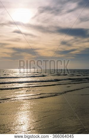 Beach With A Calm Sea And A Spectacular Sky At Sunset, The Sun Reflects On The Water And There Is A