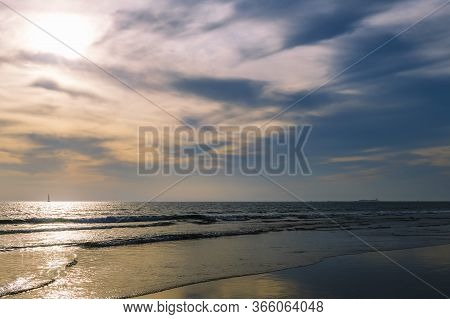 Seascape Of A Beach With A Calm Sea And A Spectacular Sky At Sunset, The Sun Reflects On The Water A