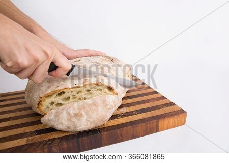 Person Cutting Freshly Baked Crusty Bread In Slices. Closeup Of Hands And Knife. Isolated Object On