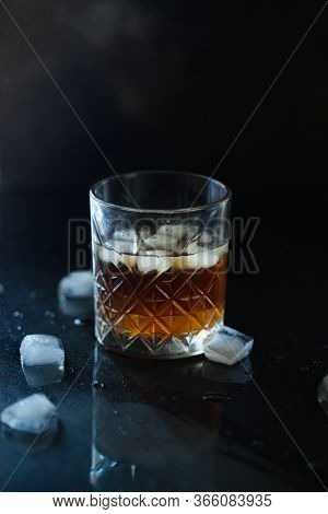 Glass Of Whiskey Or Bourbon With Ice On Black Stone Table. Glass Of Whiskey With Ice And A Square De