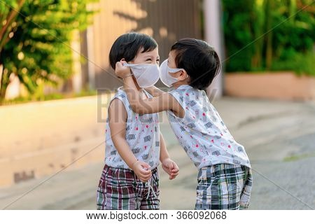Kid In Safety Wearing Mask In Town. Twin Children Wearing Medical Face Mask Outdoor. Twin Child  Hel