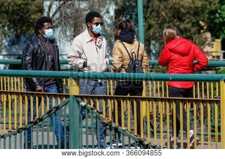 Uzhgorod, Ukraine - May 12, 2020: People In Protective Masks Walk On The Footbridge After Weakening