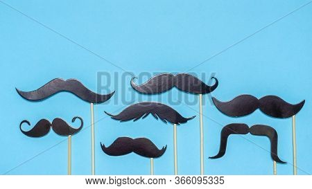 Various Black Photo Booth Props Moustaches Of Different Shape On Blue Background. Greeting Card For