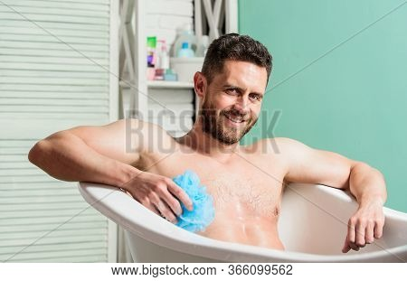 Macho Naked In Bathtub. Sex And Relaxation Concept. Wash Off Foam With Water Carefully. Man Wash Mus