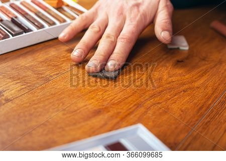 Repair And Restoration Of Laminate And Parquet. Sealing Scratches And Chips. The Master Erases A Wor