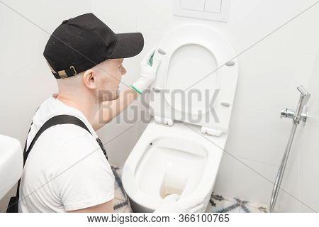 Plumber Installing Toilet Bowl In Restroom, Work In Bathroom