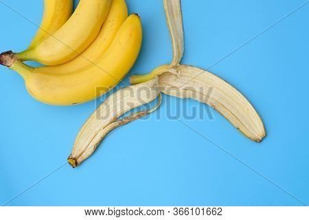 A Bunch Of Bananas And Peel From A Banana On A Blue Background. The Benefits Of Eating Bananas, Diet