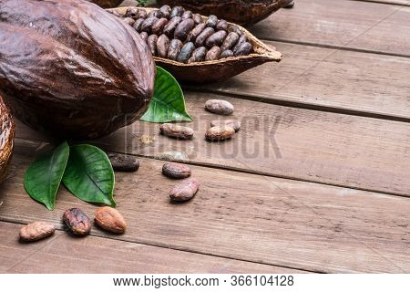 Cocoa pod and cocoa beans on the wooden table. Top view.