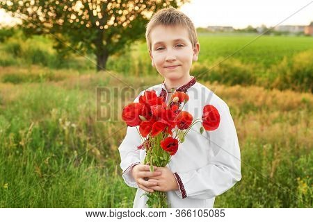 Ukraine's Independence Day. Child Boy In An Embroidered Shirt With Bouquet Of Poppies. Ukraine In Fi