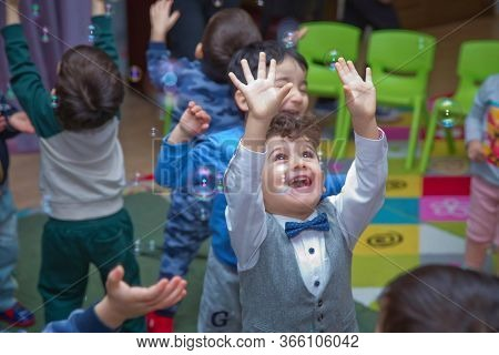 Cute Little Boy Catching Soap Bubbles . Little Blonde Boy Playing With Soap Bubbles . Children At Th