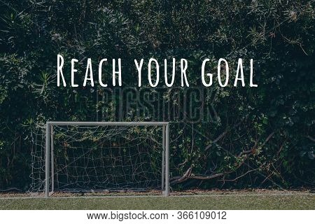 Soccer Goal At The Outdoor Amateur Field Surrounded By Green Plant Wall. Reach You Goal Wording. Clo