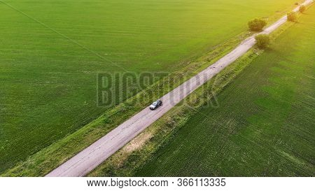 Aerial. Local Tourism Concept With Car Driving Along The Rural Road Between Two Fields. View Above.