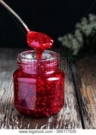 Homemade Raspberry Jam In A Glass Jar On A Wooden Table. Close-up, Selective Focus. Spoon With Jam O