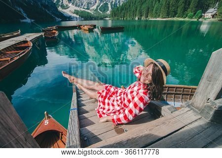Woman In Red Sundress Sitting On Wooden Stairs Looking At Lake In Mountains