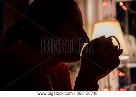 Silhouette Of A Girl With Closed Eyes Holding A White Cup With A Warm Drink And Drinking With Pleasu