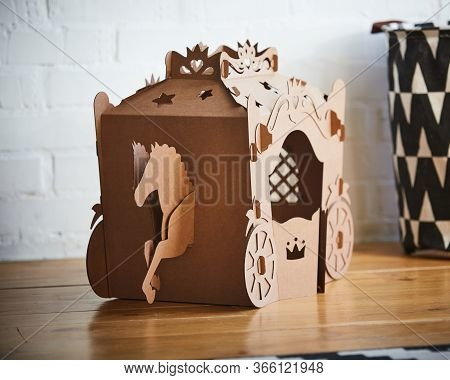 A Horse And A Carriage Made Of Brown Cardboard, Where The Horse Is Pulling The Carriage.