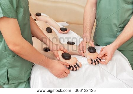 Woman Receiving Hot Stones Massage On Legs In Four Hands By Two Massage Therapists.
