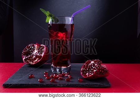 Pomegranate Juice With A Straw And A Leaf Of Mint. Fresh Pomegranate Juice And Fruits. Scattered Pom