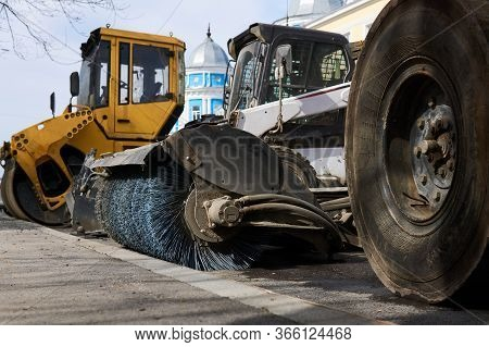 Heavy Road Equipment Stands On The Sidelines Against The Background Of The City, Close-up